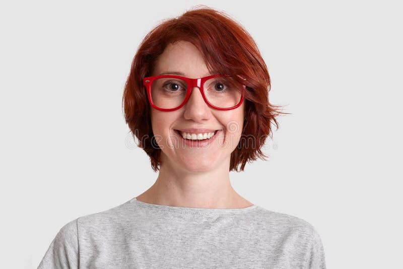 Sluit omhoog geschoten van glimlachende blije vrouw met kort kapsel, draagt rood rimed terloops geklede die bril, over wit wordt  stock fotografie