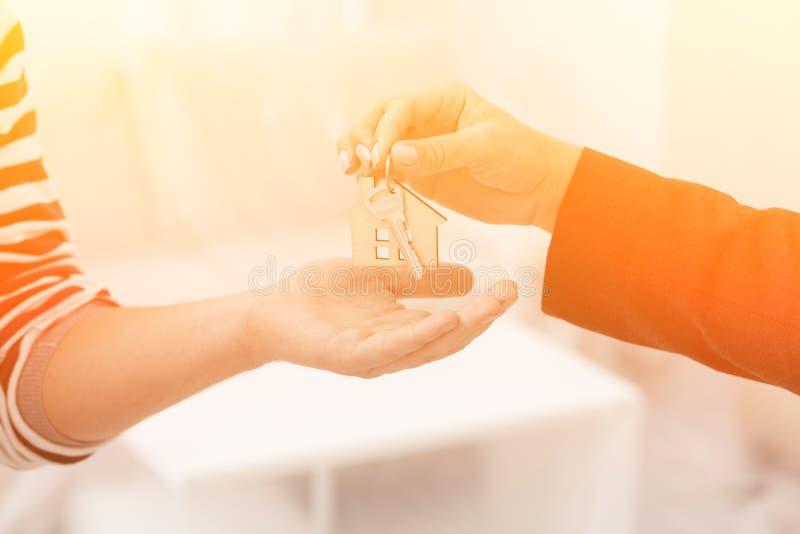 Sluit omhoog geschoten van handen die sleutels van een flat geven royalty-vrije stock afbeelding