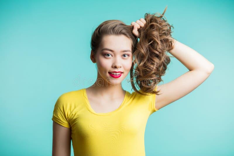 Sluit omhoog geschoten van het modieuze jonge vrouw glimlachen tegen blauwe achtergrond Het mooie vrouwelijke model verzamelde ha stock afbeelding