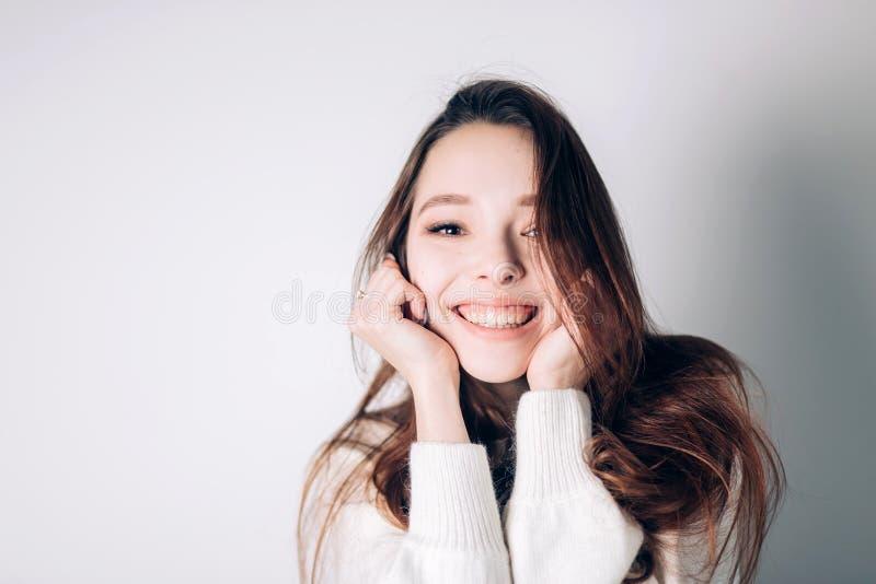 Sluit omhoog geschoten van het modieuze jonge vrouw glimlachen tegen witte achtergrond Mooi vrouwelijk model die de camera bekijk royalty-vrije stock fotografie
