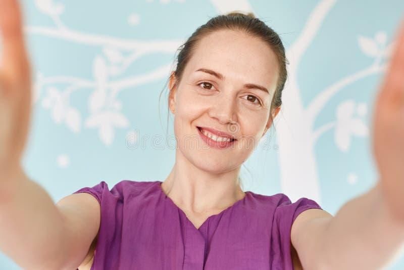 Sluit omhoog geschoten van knappe glimlachende jonge vrouw gekleed in toevallige purpere t-shirt, stelt voor het maken selfie, te royalty-vrije stock afbeeldingen