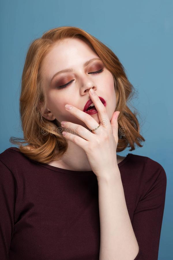 Sluit omhoog geschoten van modieuze jonge vrouw tegen blauwe achtergrond Roodharigemeisje met gesloten ogen makeup royalty-vrije stock afbeeldingen
