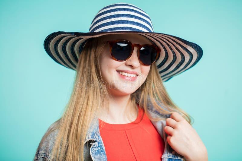 Sluit omhoog geschoten van modieuze vrouw die in zonnebril tegen blauwe achtergrond glimlachen Mooie vrouwelijke model gestreepte royalty-vrije stock foto's