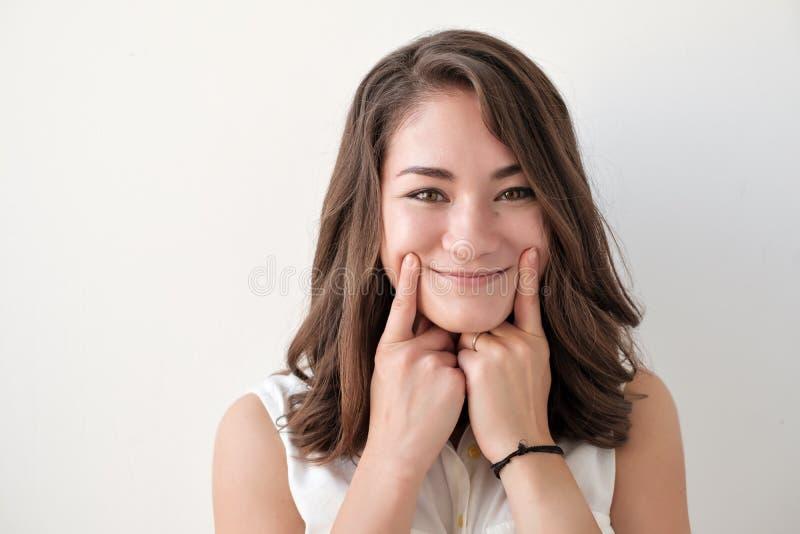 Sluit omhoog geschoten van mooie tiener die een glimlach dwingen, die haar vingers houden dichtbij lippen, kijkend met gelukkige  stock afbeeldingen