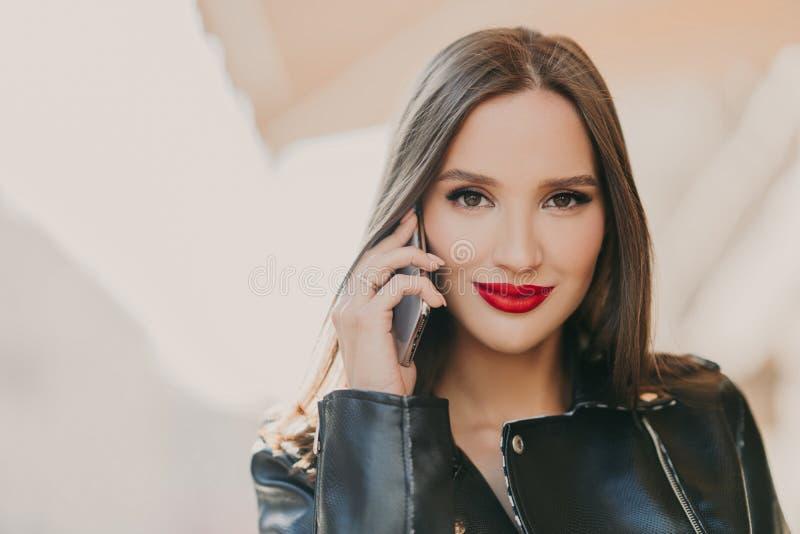 Sluit omhoog geschoten van mooie vrouwenbesprekingen met vriend via mobiele toepassing, heeft make-up en de rode lippen, gekleed  stock foto's