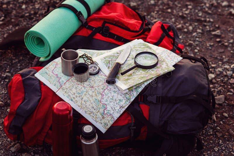 Sluit omhoog geschoten van reismateriaal, rugzak, kaart, kompas, mes, die stootkussen slapen ter plaatse bij berg Reeks van stock afbeelding