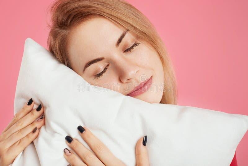 Sluit omhoog geschoten van vermoeid wijfje die slaperig en vermoei, houdt zacht wit hoofdkussen, leunt bij het zijn zoals wil om  stock foto