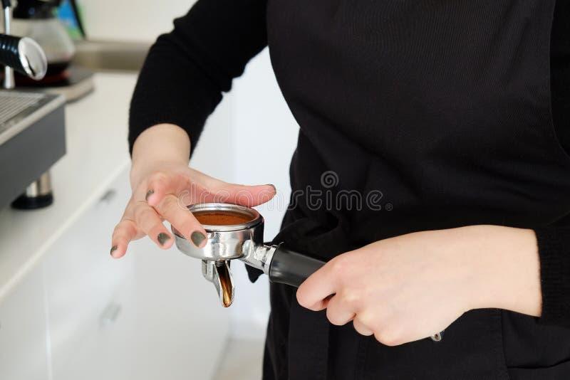 Sluit omhoog geschoten van vrouwelijke barista in proces om koffiedrank te maken stock afbeelding
