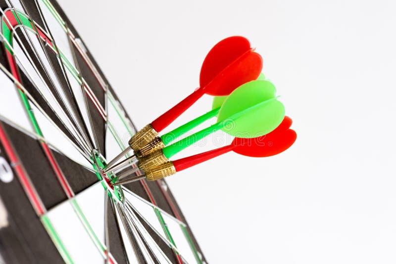 Sluit omhoog geschotene groene en rode pijltjespijlen in het doelcentrum stock afbeeldingen