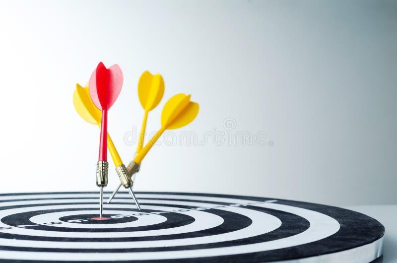 Sluit omhoog geschotene rode pijltjepijl op centrum van dartboard en gele a stock foto's