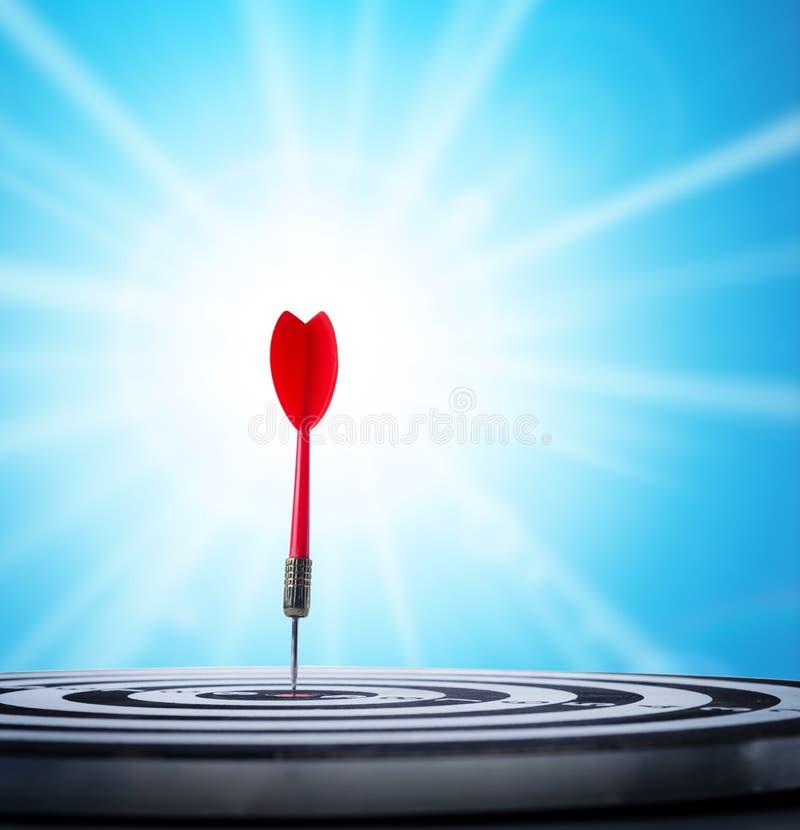 Sluit omhoog geschotene rode pijltjepijl op centrum van dartboard over zonnestraal royalty-vrije stock foto