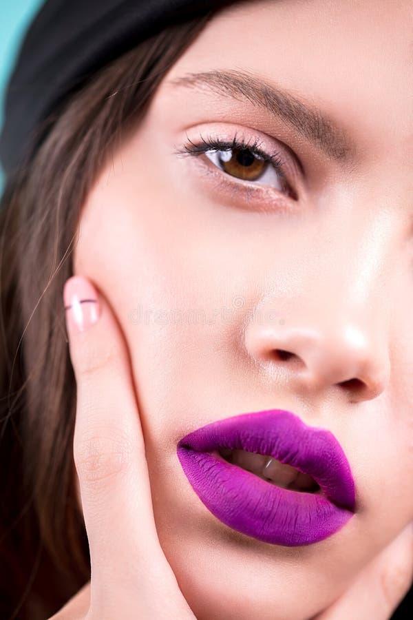 Sluit omhoog gezicht van een mooie jonge donkerbruine vrouw met professionele make-up, goed verzorgd gezicht, purpere lippen Mani royalty-vrije stock afbeeldingen