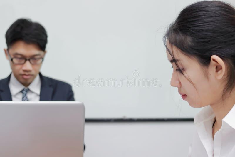 Sluit omhoog gezicht van ongelukkige Aziatische bedrijfsvrouw die conflict met haar collega in bureau hebben royalty-vrije stock foto's