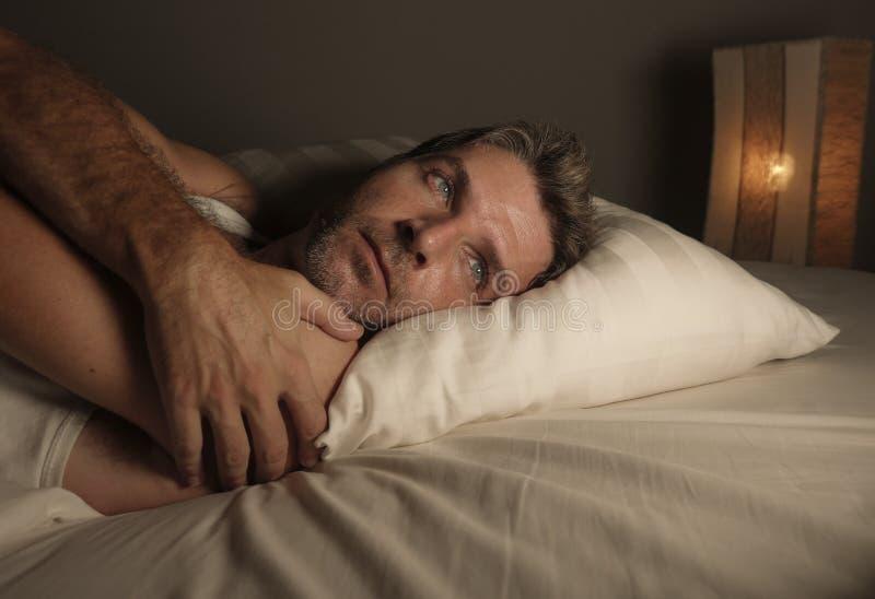 Sluit omhoog gezichtsportret die van de aantrekkelijke droevige en nadenkende mens op bed wakker laat bij nacht het denken ongeru royalty-vrije stock foto's