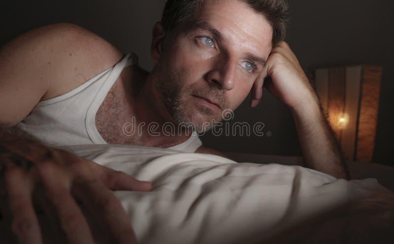 Sluit omhoog gezichtsportret die van de aantrekkelijke droevige en nadenkende mens op bed wakker laat bij nacht het denken ongeru stock foto