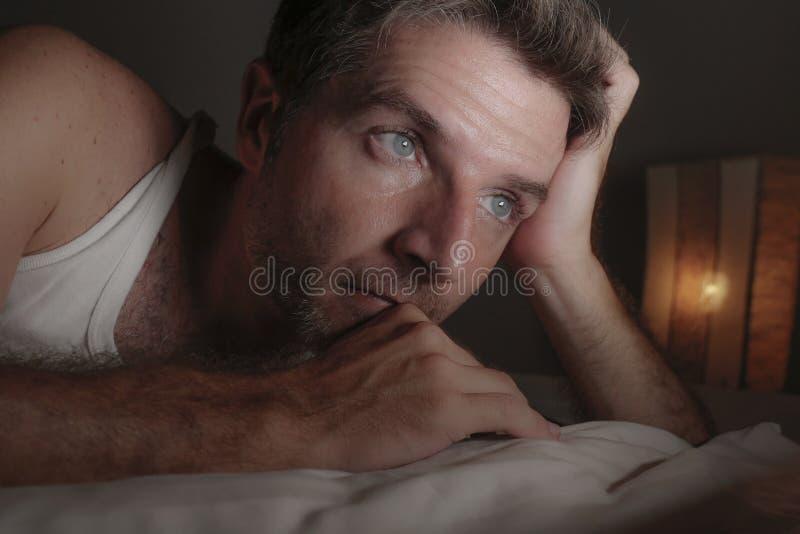 Sluit omhoog gezichtsportret die van de aantrekkelijke droevige en nadenkende mens op bed wakker laat bij nacht het denken ongeru royalty-vrije stock fotografie