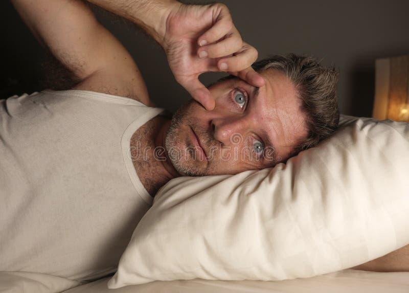 Sluit omhoog gezichtsportret van de slapeloze en wakkere aantrekkelijke mens met ogen brede open bij nacht die op bed liggen die  stock foto