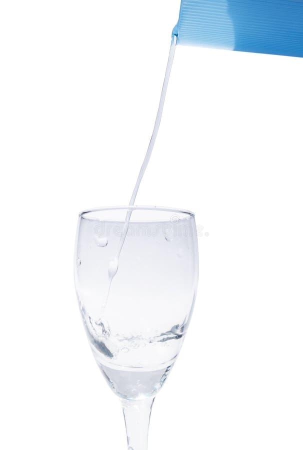 Sluit omhoog gietend die water in wijnglas, op witte achtergrond wordt geïsoleerd stock foto's