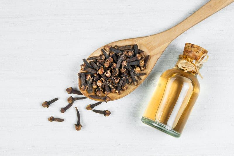 Sluit omhoog glasfles van kruidnagelolie en kruidnagels in houten lepel op witte rustieke lijst royalty-vrije stock afbeeldingen