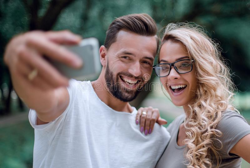 Sluit omhoog glimlachend jong paar die selfie in stadspark nemen stock foto's