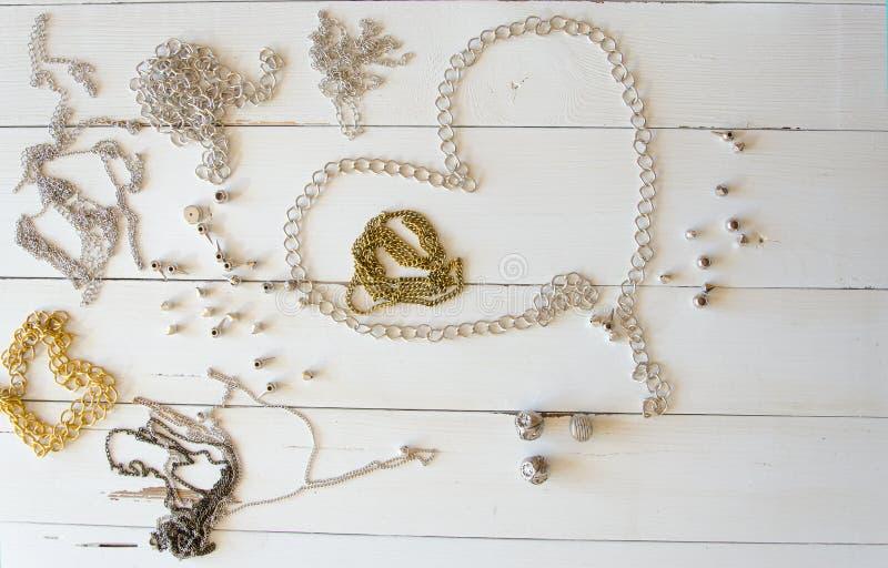 Sluit omhoog gouden halsbanden en kettingen Hand - de gemaakte de elementenvlakte van metaaljuwelen lag royalty-vrije stock foto