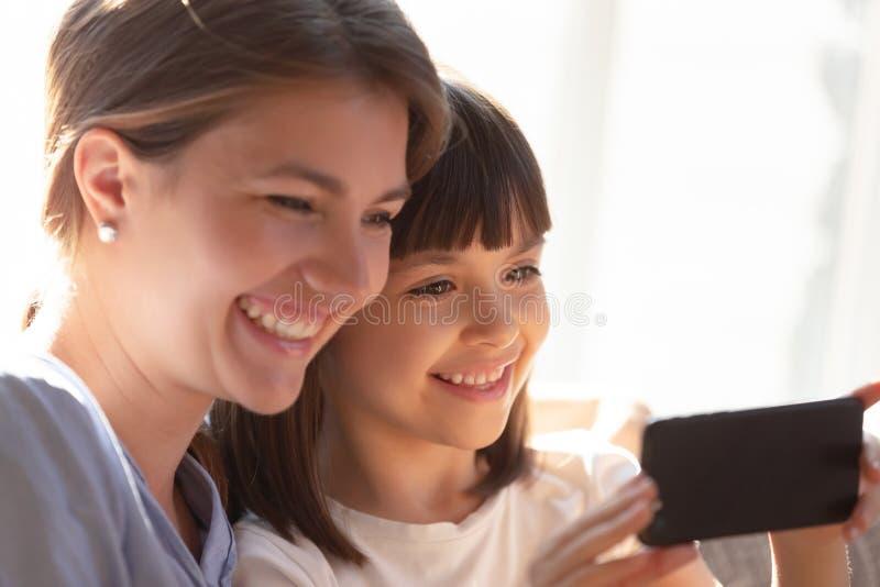 Sluit omhoog grappige moeder en dochter die het smartphonescherm bekijken royalty-vrije stock afbeelding