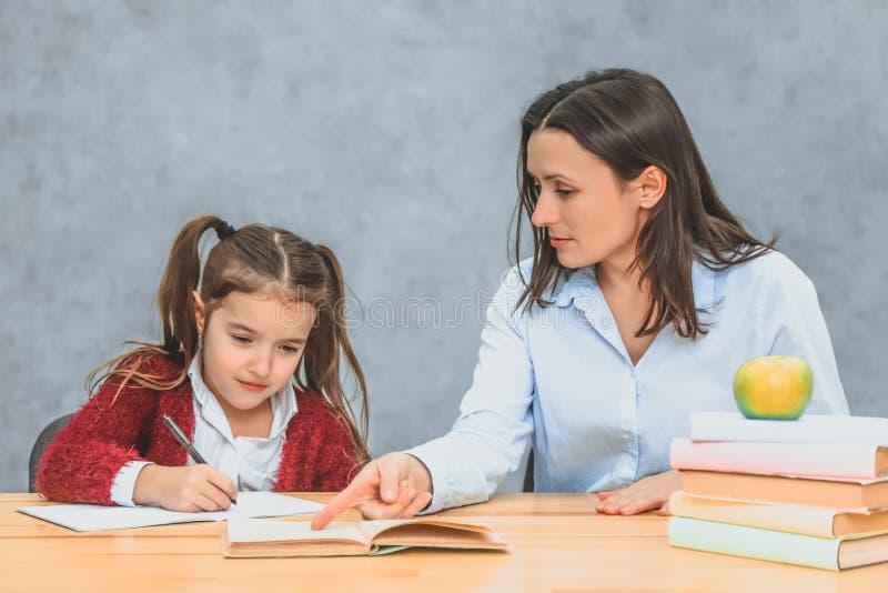 Sluit omhoog grappige moeder en kinddochter die en thuiswerk doen die thuis schrijven lezen stock fotografie