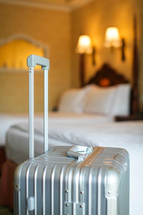 Sluit omhoog grijze zilveren reiskoffer is in een onbezette hotelruimte en er is witte linnendekking stock foto