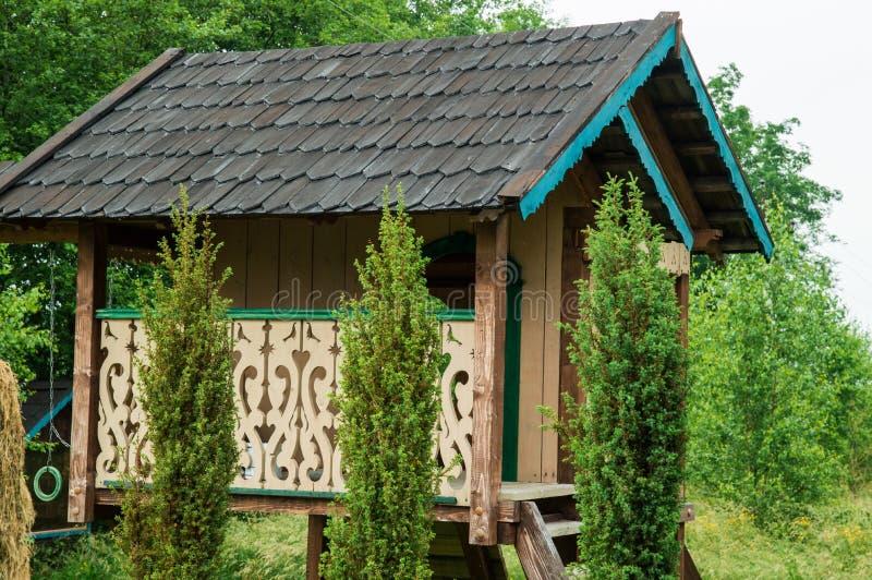 Sluit omhoog Groene de zomeryard Het houten huis van de ecoboom met gesneden uitstekend traliewerk royalty-vrije stock afbeelding