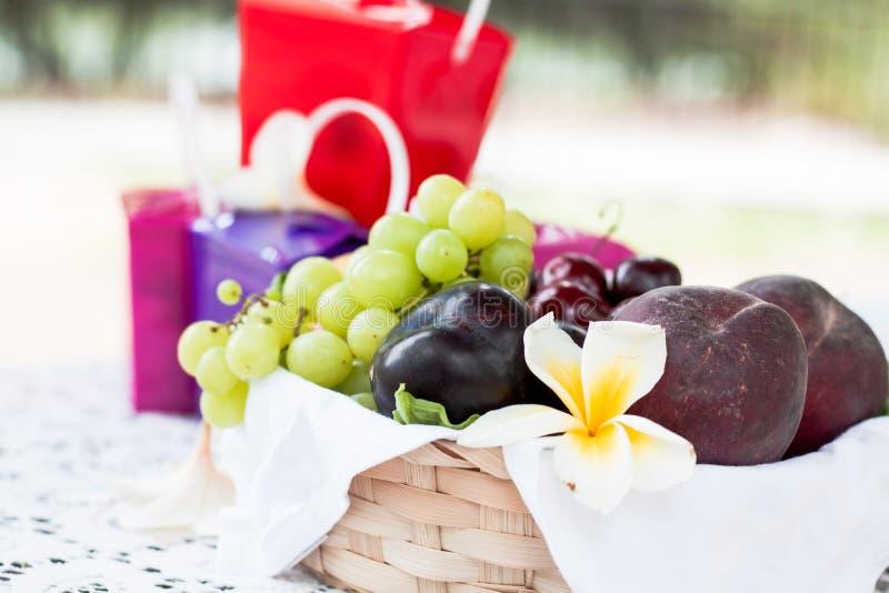 Sluit omhoog groene druiven, pruimen en kersenvruchten in houten baske royalty-vrije stock foto