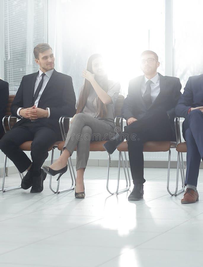 Sluit omhoog groep bedrijfsmensen die in hal van bureau zitten royalty-vrije stock fotografie