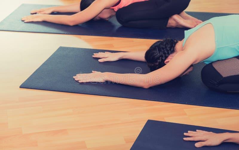 Sluit omhoog groep mensen die yogakind ` s doen stelt in studiotrai stock fotografie