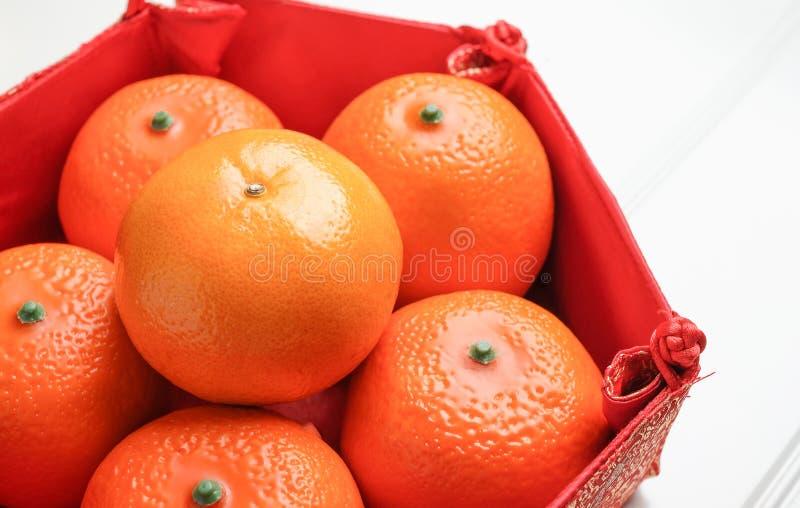 Sluit omhoog groep oranje mandarijn in Chinees patroondienblad op wh stock afbeelding
