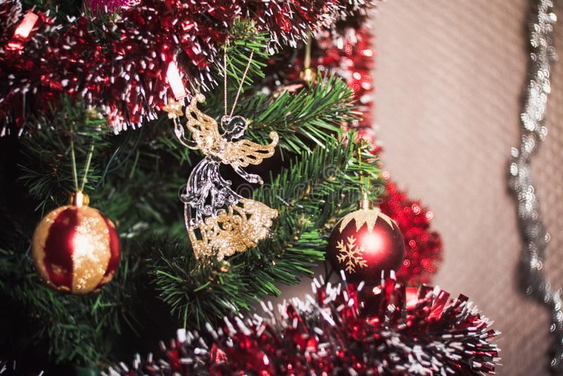 Sluit omhoog groot goud en het rood schittert bal en glasengelenkerstmis op boom stock foto