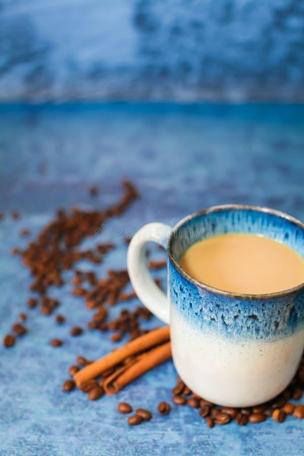 Sluit omhoog grote kop van koffie met van de melkkaneel en koffie bonen op blauwe grungeachtergrond royalty-vrije stock fotografie
