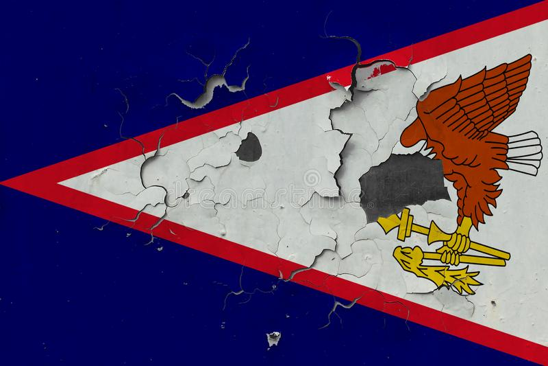 Sluit omhoog grungy, beschadigde en doorstane Amerikaanse vlag van Samoa bij de muurschil van verf om binnenoppervlakte te zien stock fotografie