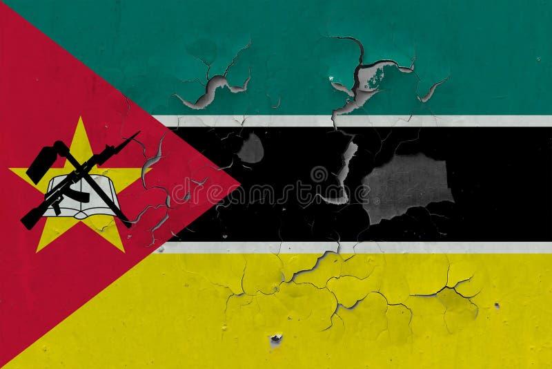 Sluit omhoog grungy, beschadigde en doorstane vlag van Mozambique bij de muurschil van verf om binnenoppervlakte te zien stock illustratie