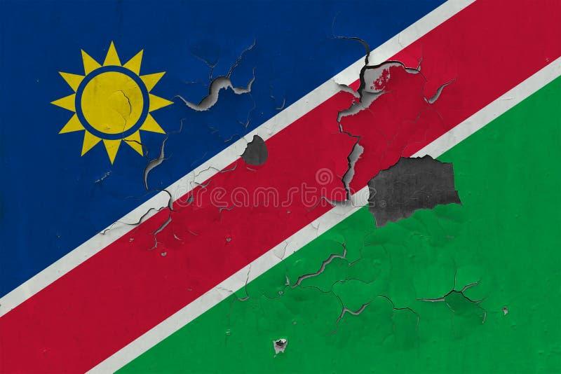 Sluit omhoog grungy, beschadigde en doorstane vlag van Namibië bij de muurschil van verf om binnenoppervlakte te zien stock illustratie
