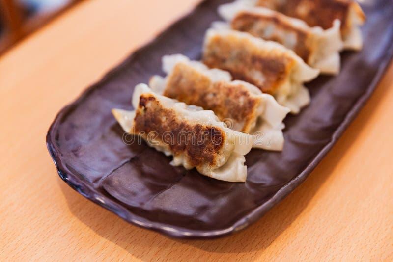 Sluit omhoog Gyoza Japans die Pan-Fried Dumplings met saus en sesamolie wordt gediend stock foto's