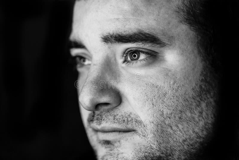 Sluit omhoog half zijportret van een jonge mens Het schot van de studio geleide ringsbezinning in de ogen royalty-vrije stock fotografie