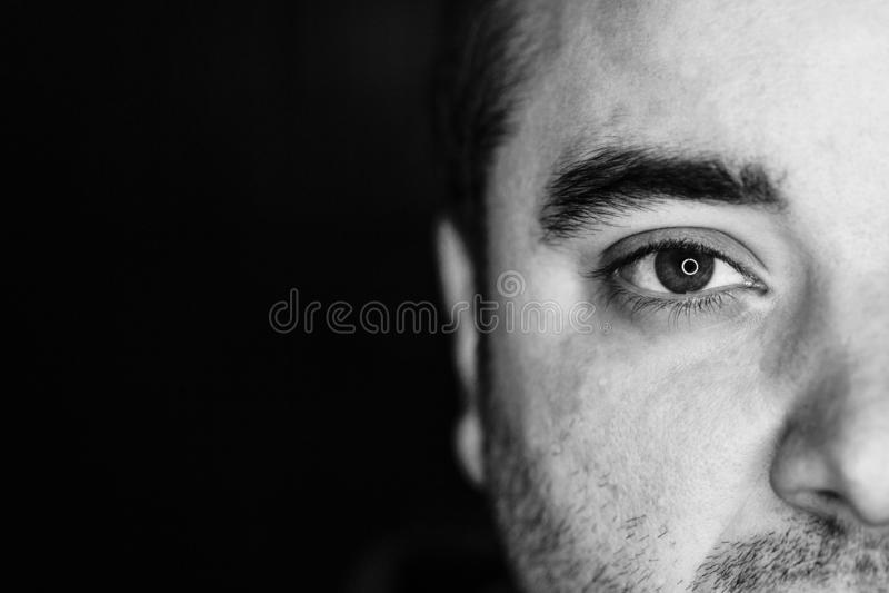 Sluit omhoog half zijportret van een jonge mens Het schot van de studio geleide ringsbezinning in de ogen stock foto's