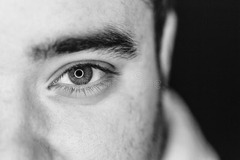 Sluit omhoog half zijportret van een jonge mens Het schot van de studio geleide ringsbezinning in de ogen royalty-vrije stock afbeeldingen