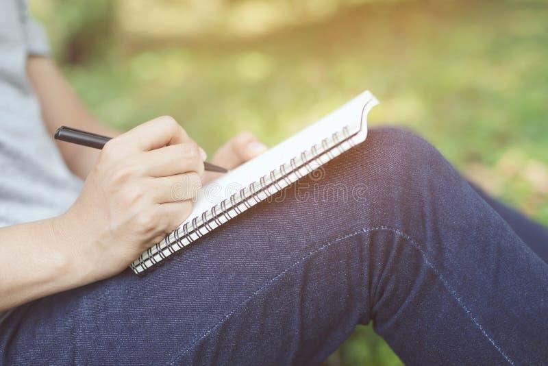 Sluit omhoog hand de jonge mens op een marmeren stoel zit het gebruiken van pen het schrijven de notastootkussen van de Verslagle royalty-vrije stock foto