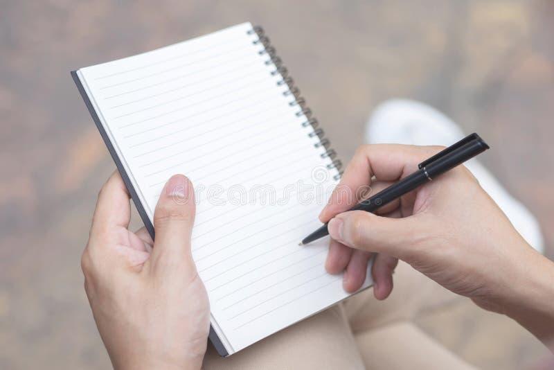 Sluit omhoog hand de jonge mens pen het schrijven de notastootkussen van de Verslaglezing in de boekzitting op de stoel openlucht royalty-vrije stock afbeelding