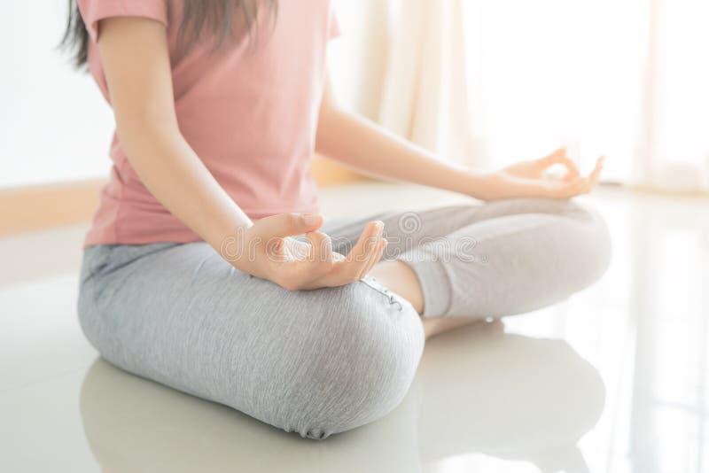 Sluit omhoog hand en het halve lichaam van gezonde vrouw zit de positie van de lotusbloemyoga Jonge gezonde de houdingsoefening v stock foto's