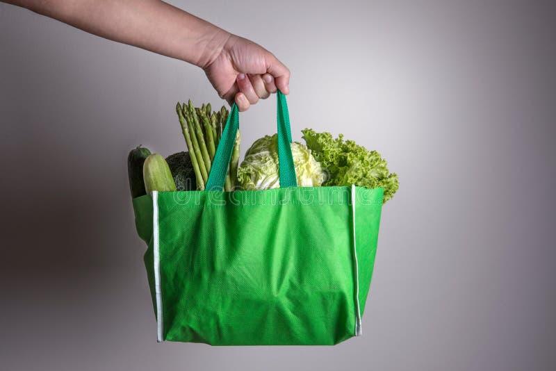 Sluit omhoog hand houdend de groene kruidenierswinkelzak van organische gre mengde royalty-vrije stock afbeelding