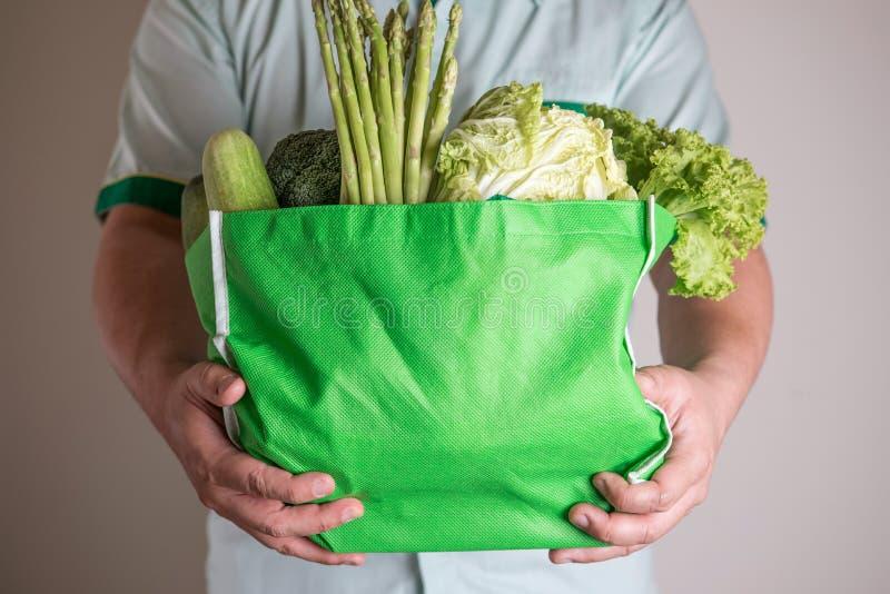 Sluit omhoog hand houdend de groene kruidenierswinkelzak van organische gre mengde stock fotografie