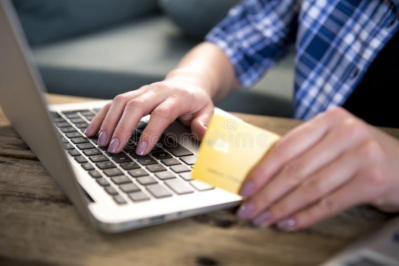 Sluit omhoog hand van de creditcard van de vrouwenholding online winkelen of het beleggen op Internet met laptop computer thuis i stock afbeeldingen