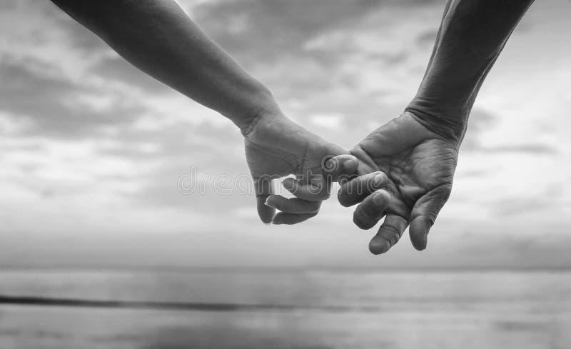 Sluit omhoog hand van hogere paarhaak elkaar & x27; s pink samen dichtbij kust bij het strand, zwart-wit beeld stock afbeeldingen
