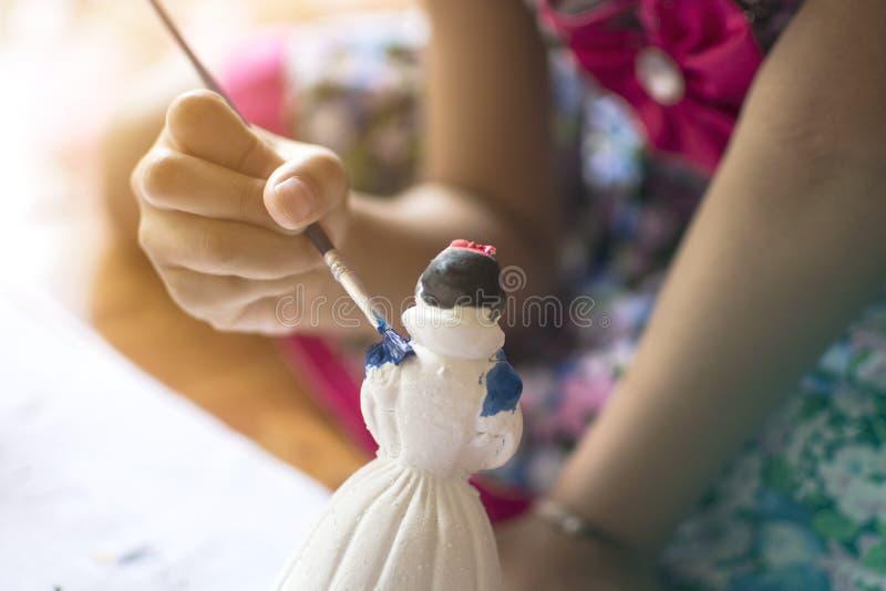 Sluit omhoog hand van meisje het schilderen pleisterpop met blauwe waterkleur royalty-vrije stock afbeeldingen